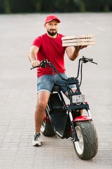 Voller schuss-lieferbote, der pizzakästen hält