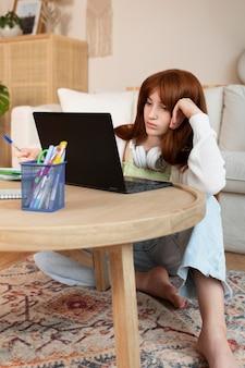 Voller schuss mädchen lernen mit laptop auf dem boden