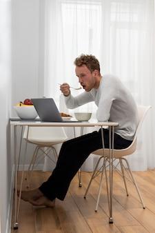 Voller schuss mann, der am tisch isst