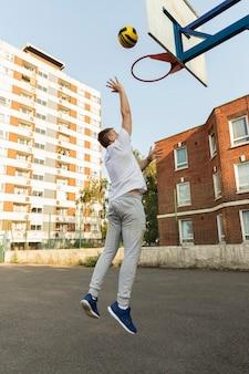 Voller schuss mann, der basketball spielt