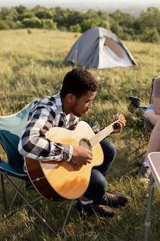 Voller schuss mann, der gitarre spielt