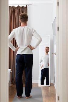 Voller schuss mann, der in den spiegel schaut