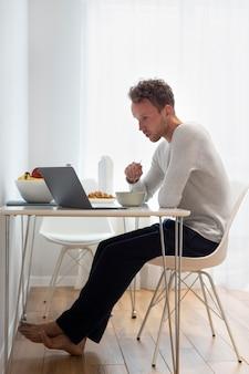 Voller schuss mann, der isst und arbeitet
