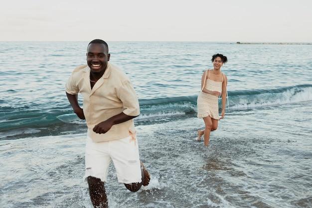 Voller schuss mann läuft am strand Kostenlose Fotos