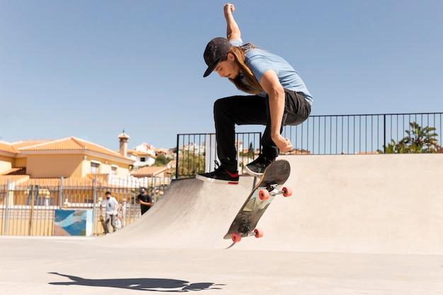 Voller schuss mann macht tricks mit skateboard skate