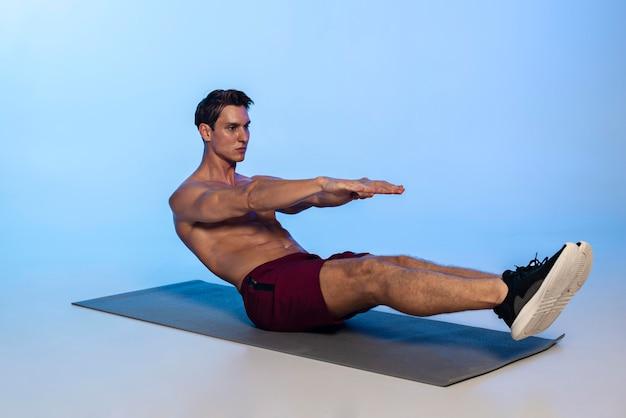 Voller schuss mann trainiert bauchmuskeln