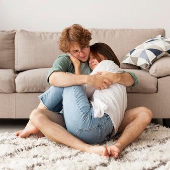 Voller schuss niedliches paar, das auf teppich umarmt