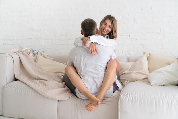 Voller schuss paar umarmt auf der couch