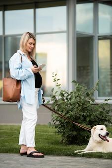 Voller schuss schwangere frau mit süßem hund