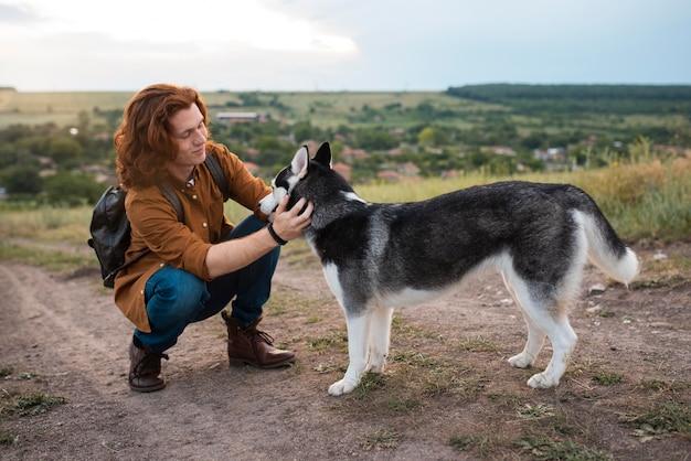 Voller schuss smiley-mann, der hund streichelt