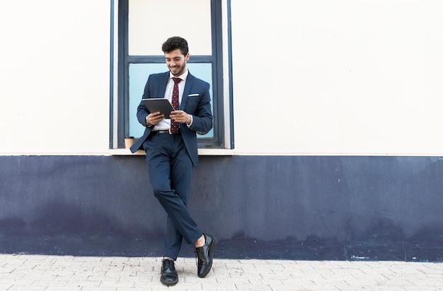 Voller schuss stehender mann mit seiner tablette