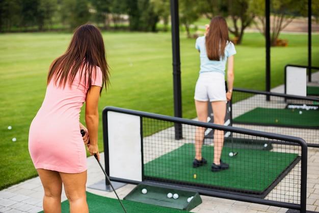 Voller schuss von den frauen, die golf üben