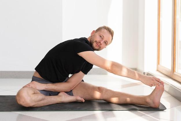 Voller schussmann, der auf yogamatte streckt