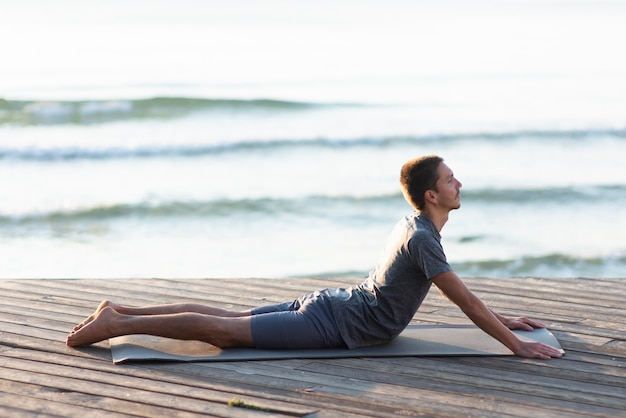 Voller schussmann, der yoga-haltung nahe meer praktiziert