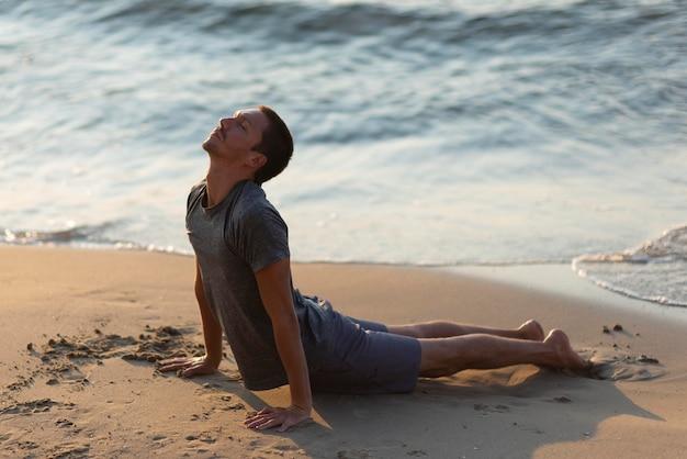 Voller schussmann, der yoga-pose am strand tut