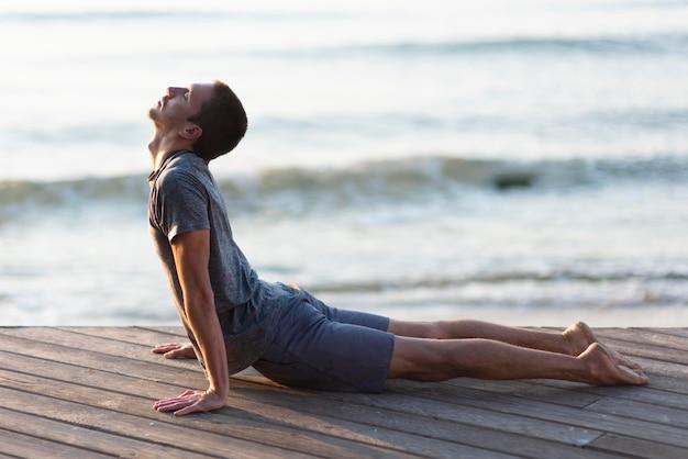Voller schussmann, der yoga-pose auf dock nahe meer praktiziert