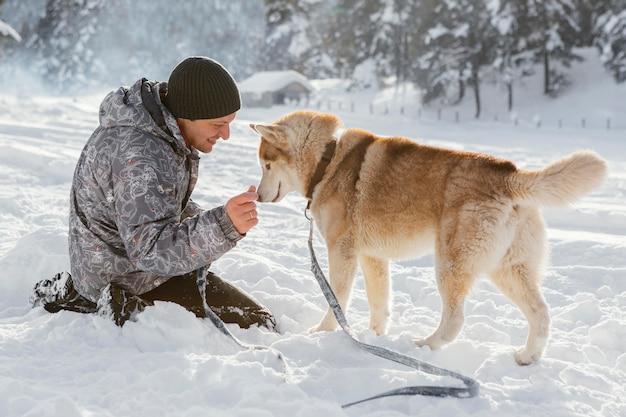 Voller schussmann mit hund im schnee