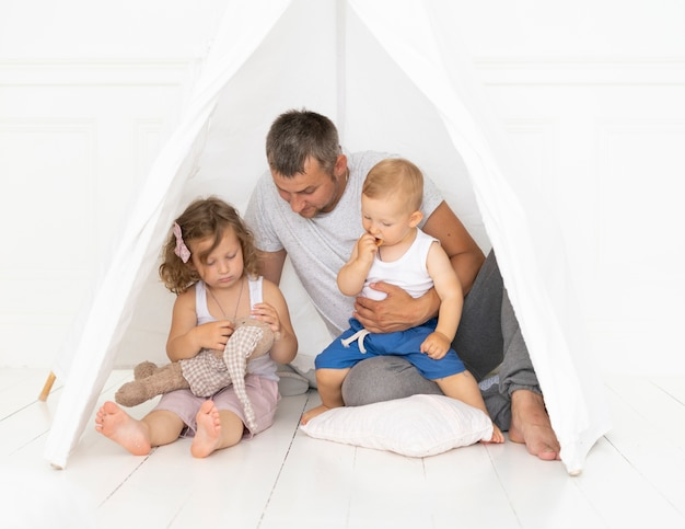 Voller schussvater, der mit seinem kind in einem zelt spielt