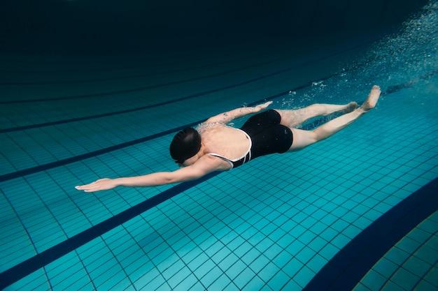 Voller schwimmer im pool mit mütze