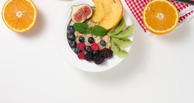 Voller teller mit haferflocken und orangenfrüchten auf einem weißen tisch. gesundes frühstück, draufsicht