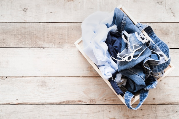 Voller wäschekorb der draufsicht mit hölzernem hintergrund