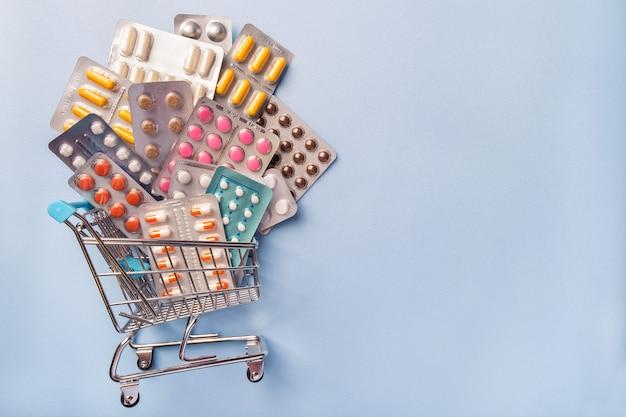 Voller wagen von der apotheke mit medikamenten und pillen auf blauem hintergrund mit kopienraum. einkaufswagen mit drogen und tablette. online-shop mit lieferung.
