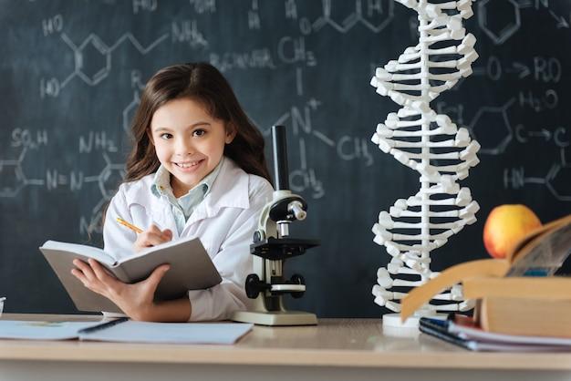 Voller wissenschaftlicher ideen. erfinderisch entzückter niedlicher schüler, der im labor sitzt und naturwissenschaftlichen unterricht hat, während er studiert und notizen macht