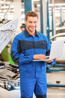 Voller zuversicht und kompetenz. selbstbewusster junger mann, der am laptop arbeitet und lächelt, während er in der werkstatt mit dem auto im hintergrund steht