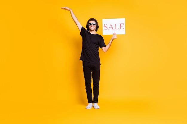 Volles bein foto des jungen mannes stand halten poster verkauf heben hand leeren raum tragen schwarze t-shirt hose weiße turnschuhe sonnenbrille isoliert gelber hintergrund