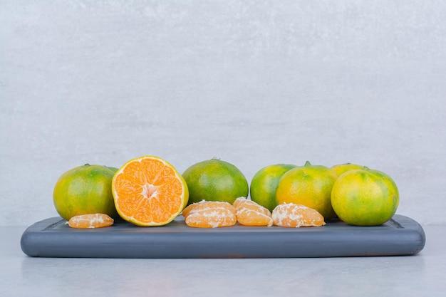 Volles dunkles schneidebrett der sauren mandarinen auf weiß