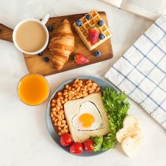 Volles englisches frühstück mit spiegeleiern, bohnen, toast, salat, tomaten auf weiß
