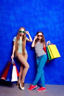 Volles foto von zwei trendigen frauen in gläsern, die einkaufstaschen halten