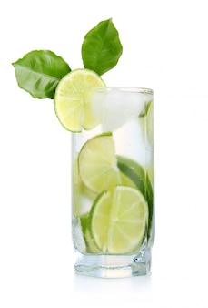 Volles glas frisches kühles stärkungsmittel mit den kalkfrüchten lokalisiert
