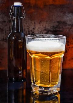 Volles glas helles bier und bierflasche auf einer schwarzen spiegeloberfläche. lebensmittel- und getränkekonzept