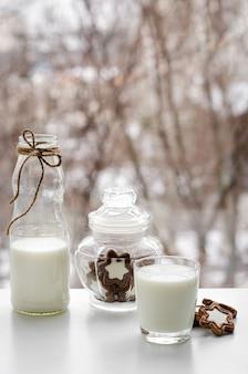 Volles glas milch, schokoladenkekse und eine flasche auf frühstückstisch auf fensteransicht.