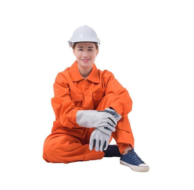 Volles körperporträt einer arbeitnehmerin im mechaniker jumpsuit sitzt