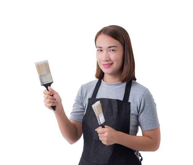 Volles körperporträt einer arbeitskraftfrau oder der servicewoman im grauen hemd und im schutzblech hält pinsel lokalisiert auf weißem hintergrund