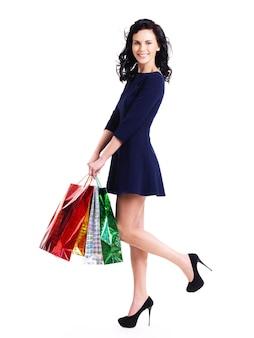 Volles porträt der glücklichen frau mit einkaufstaschen im blauen kleid, das lokal auf weißer wand steht.