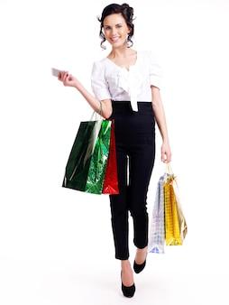 Volles porträt der glücklichen frau mit farbeinkaufstaschen, die lokalisiert auf weißer wand stehen.
