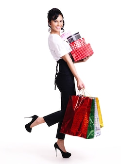 Volles porträt der glücklichen frau mit farbeinkaufstaschen und -kästen, die lokalisiert auf weißem hintergrund stehen.