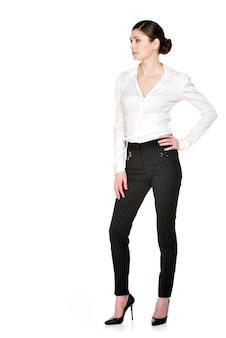 Volles porträt der jungen schönen frau im weißen hemd und in den schwarzen hosen stehend.