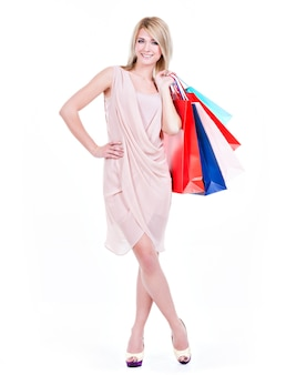 Volles porträt der lächelnden jungen blonden frau mit den bunten einkaufstaschen im rosa kleid, das auf einem weißen hintergrund aufwirft