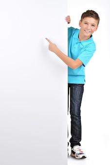 Volles porträt des fröhlichen jungen, der auf weißes plakat zeigt, das auf weiß lokalisiert wird