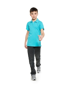 Volles porträt des gehenden jugendlich jungen im blauen t-shirt lässig auf weiß isoliert.