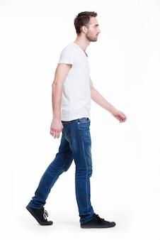 Volles porträt des gehenden mannes im weißen t-shirt lässig - lokalisiert auf weiß.