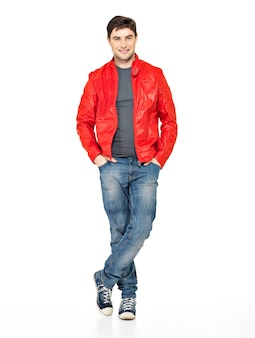 Volles porträt des lächelnden glücklichen gutaussehenden mannes in der roten jacke, in den blauen jeans und in den turnschuhen. schöner kerl, der isoliert auf weiß steht