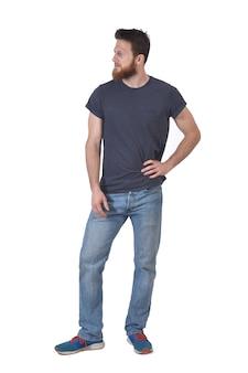 Volles porträt eines mannes mit seiner hand auf seiner taille und schauen zur seite auf weiß