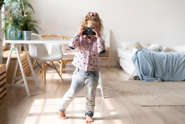Volles schussmädchen, das fotos mit kamera macht