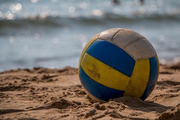 Volleyball auf gelbem sand am leeren strand in der dämmerung