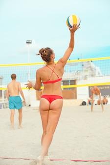 Volleyball-strandspieler ist eine sportlerin, die sich darauf vorbereitet, den ball am strand zu servieren.